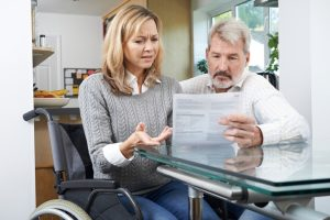 Frustrated Couple With Woman In Wheelchair Reading Disability Letter