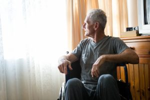 Thoughtful senior man looking away while sitting on wheelchair in nursing home